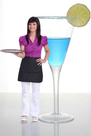 Waitress standing next to a human-sized cocktail photo