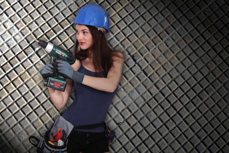 Girl with drill on squared background photo