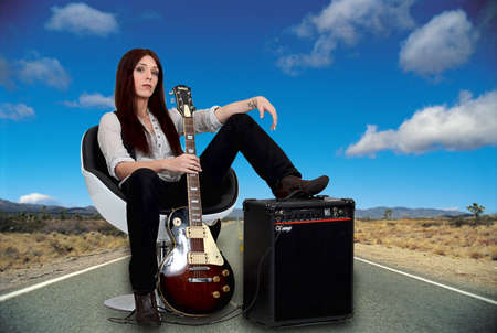 sexy guitar: Stylized female guitarist with her amp on the road Stock Photo