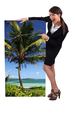 female travel agent showing poster of tropical beach photo