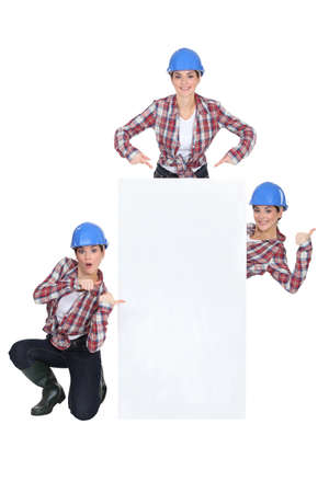 Woman in a hardhat with a board left blank for your message photo
