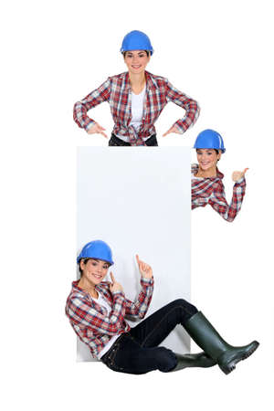 Tradeswomen surrounding a blank sign photo