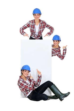 tradeswomen: Tradeswomen surrounding a blank sign