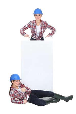tradeswomen: Tradeswomen standing around a blank sign