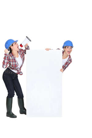 helmet construction: female worker using a megaphone Stock Photo