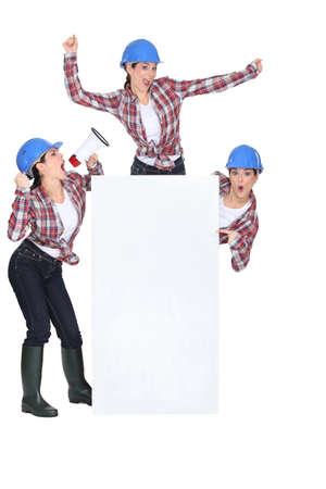 Construction woman holding blank poster photo