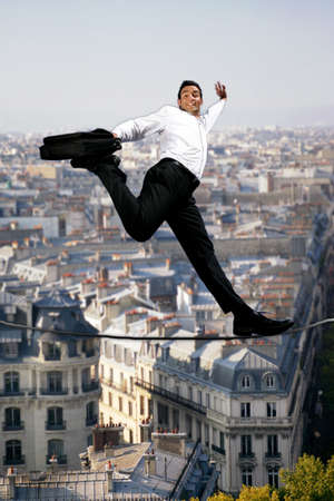 Businessman confidently walking across tight rope photo