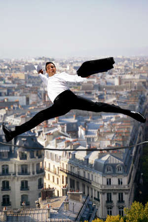 at ease: Businessman leaping across a tightrope