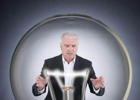 Businessman inside a light bulb photo