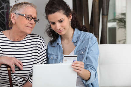 homecare helping senior woman in making online shopping Stock Photo - 13867403