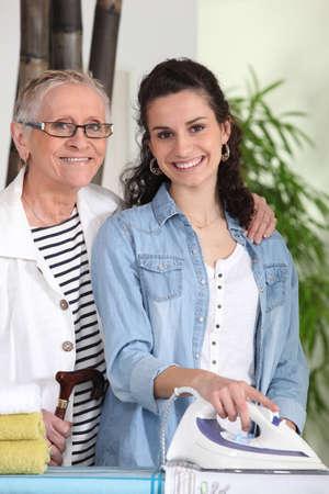 aide � la personne: Jeune femme � repasser pour une dame �g�e Banque d'images