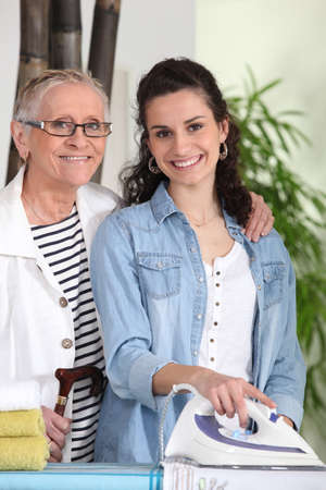 home help: Young woman ironing for an elderly lady