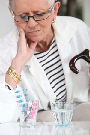 Elderly lady sat with her medication photo