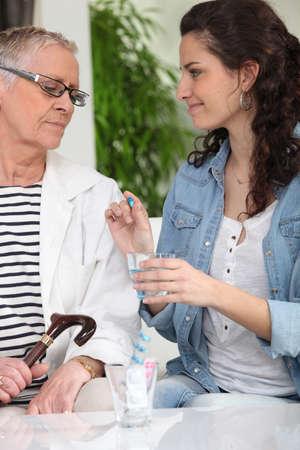 homecare giving drug to senior woman photo