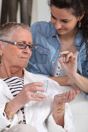 taking risks: Elderly woman taking a pill