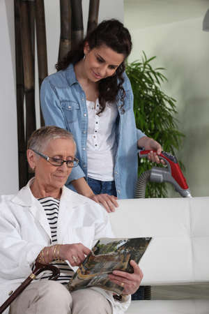 Woman vacuuming for an older lady photo