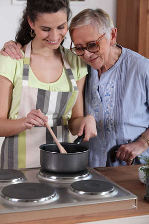 Granddaughter cooking for her grandmother photo