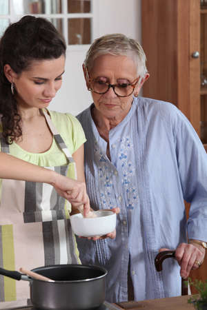 Young woman cooking with her grandmother photo