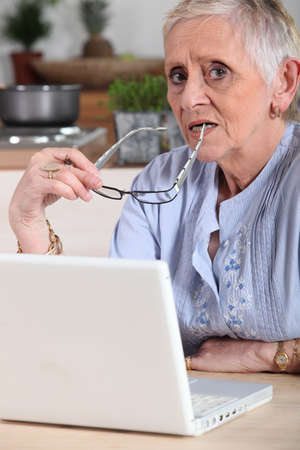 Confused old lady with laptop photo
