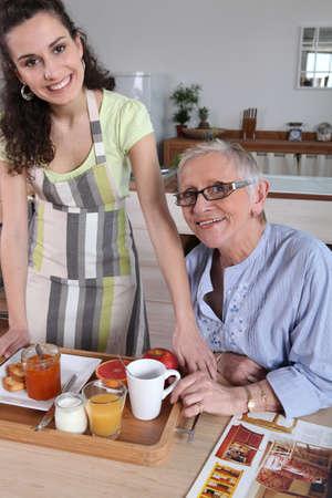 aide à la personne: Senior femme étant servi le petit déjeuner à la maison Banque d'images