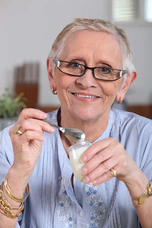 Happy senior woman eating yogurt photo