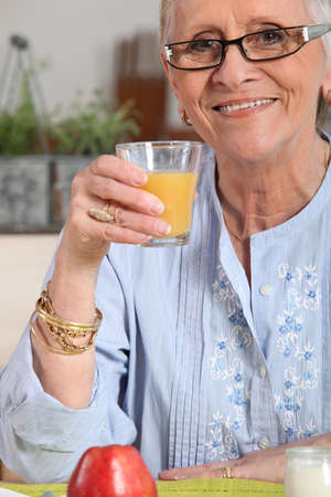 senior dame having orange juice Stock Photo