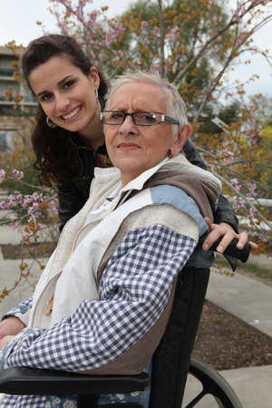 Young woman pushing an elderly lady in a wheelchair photo