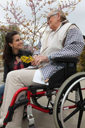 Young woman with an elderly lady in a wheelchair photo