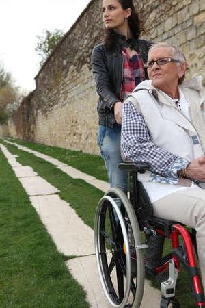 persona en silla de ruedas: Mujer joven empujando una anciana en silla de ruedas Foto de archivo