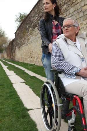 wheelchair access: Young woman pushing an elderly lady in a wheelchair