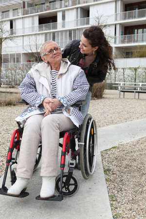 Young woman pushing an elderly woman in a wheelchair photo