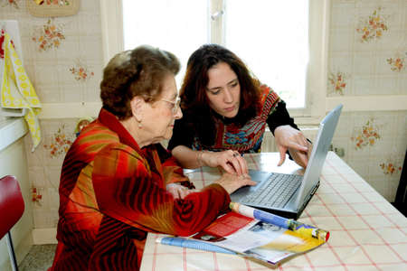Woman helping grandmother with computer photo