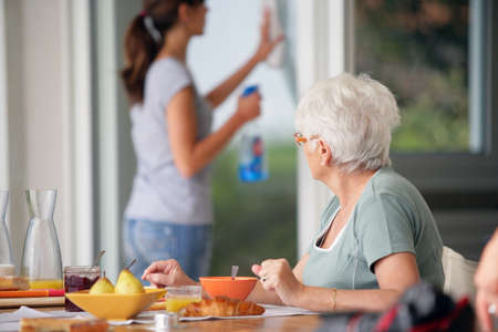 cleaning window: senior woman having breakfast with home care in the background