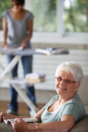 Portrait of a senior woman smiling on a sofa in front of a young woman folding laundry photo