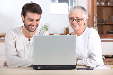 Young man and his mother using laptop photo
