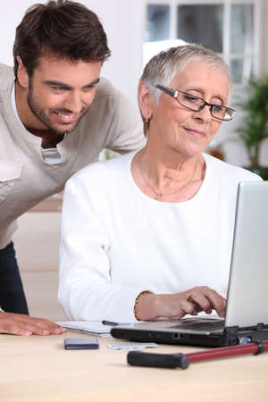 Man helping old lady with computer photo