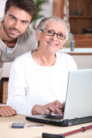 Young man helping senior woman with a laptop computer photo