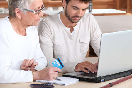 Man helping elderly family member shop on-line photo