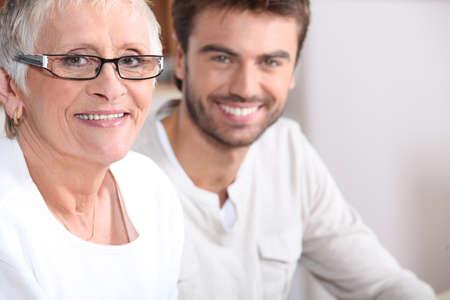 Senior Frau sitzt mit einem jungen Mann Standard-Bild