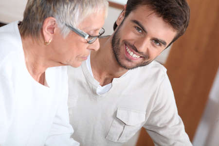 bespectacled man: An old bespectacled lady seated near a smiling young man.
