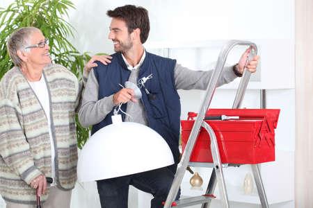 errand: Man putting up a light for a senior