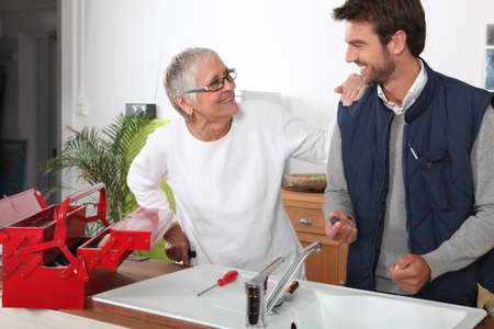 Plumber repairing sink for old lady photo