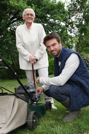 Senior with gardener and lawnmower photo