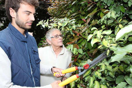 young man gardening with older woman photo