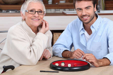 young man playing dice with older woman photo