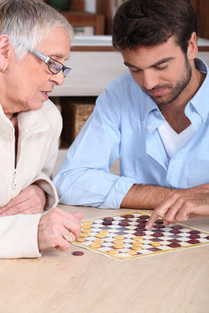concentrating: Mother and son playing checkers
