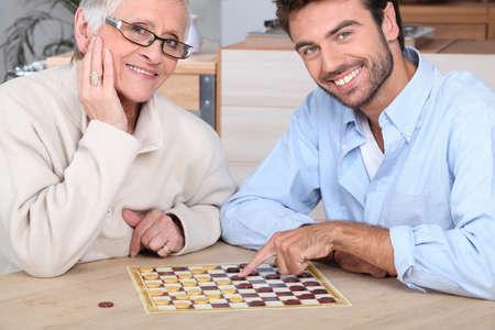aide à la personne: Jeune homme jouant de jeu avec une femme âgée