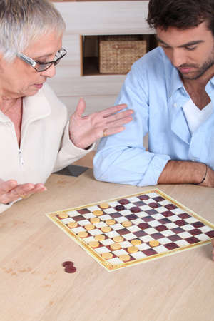 third age: Senior woman playing chess Stock Photo