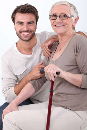 aide à la personne: Jeune homme accroupi par une femme âgée