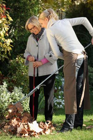 aide a domicile: Jeune femme aidant une femme �g�e � faire du jardinage Banque d'images